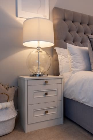 White bedside table with lamp on left side of bed