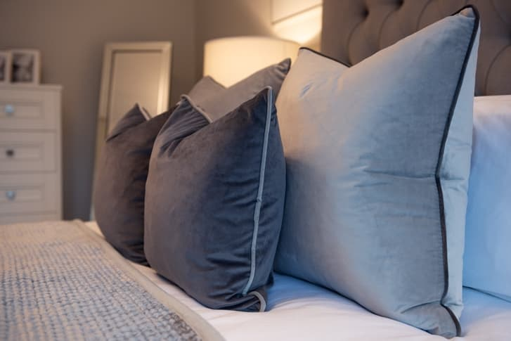 Grey and Black pillows on bed with grey throw