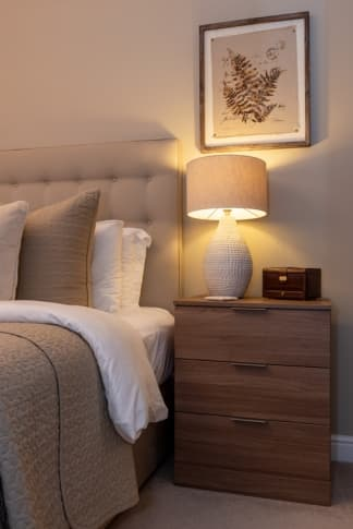 Wooden bedside table with lamp turned on
