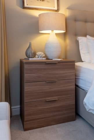 Wooden bedside table with book and light