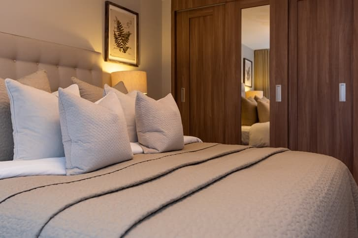 Cream pillows and throw on bed with wooden sliding wardrobes in background